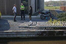 Vrouw rijdt met motor via sloot voortuin binnen